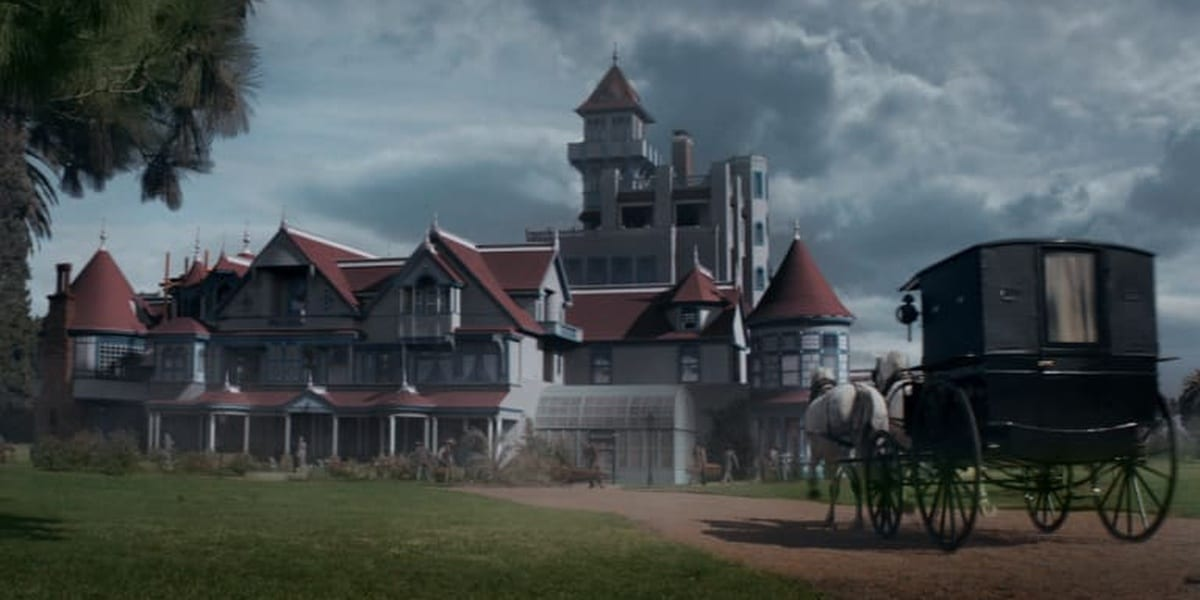 The Winchester house with clouds in the background, a horse-drawn carriage in the forefront heading down a dirt path towards the mansion
