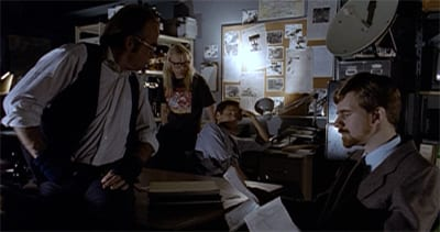 The crowded office is filled with conspiracy trappings. Four men are crowding around the room's edge.