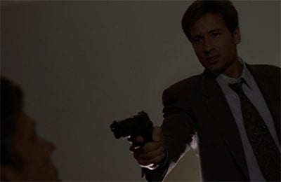 Mulder yells and brandishes a gun at CSM, who is sitting in a chair in front of him.