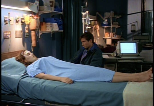 Scully lays on her hospital bed, still in a coma, while Mulder leans towards her and holds her hand.