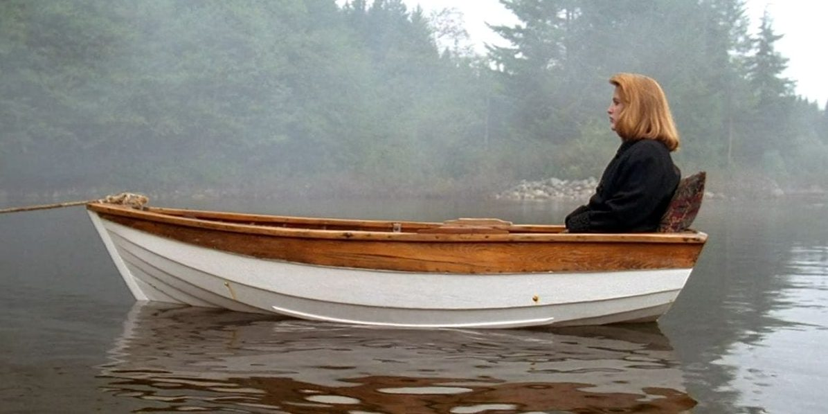 Scully in profile, on the right side of a small lifeboat, one rope holding it from drifting on the lake it floats on.