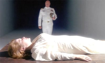 Scully lays flat on a table dressed in white on the bottom half of the frame. Behind her, also in white, is her father, dressed in white and standing straight.