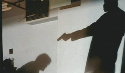 Two shadows, one of a man on the floor. The other is a man above him, pointing a gun directly at him.