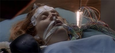 Dana Scully's head and shoulders are in frame. She's in a hospital gown, and her face has tape and tubes all over it.