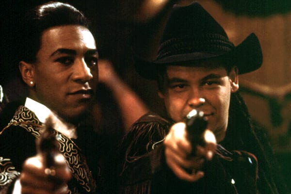 Lister and The Cat in their cowboy characters, pointing guns at the camera
