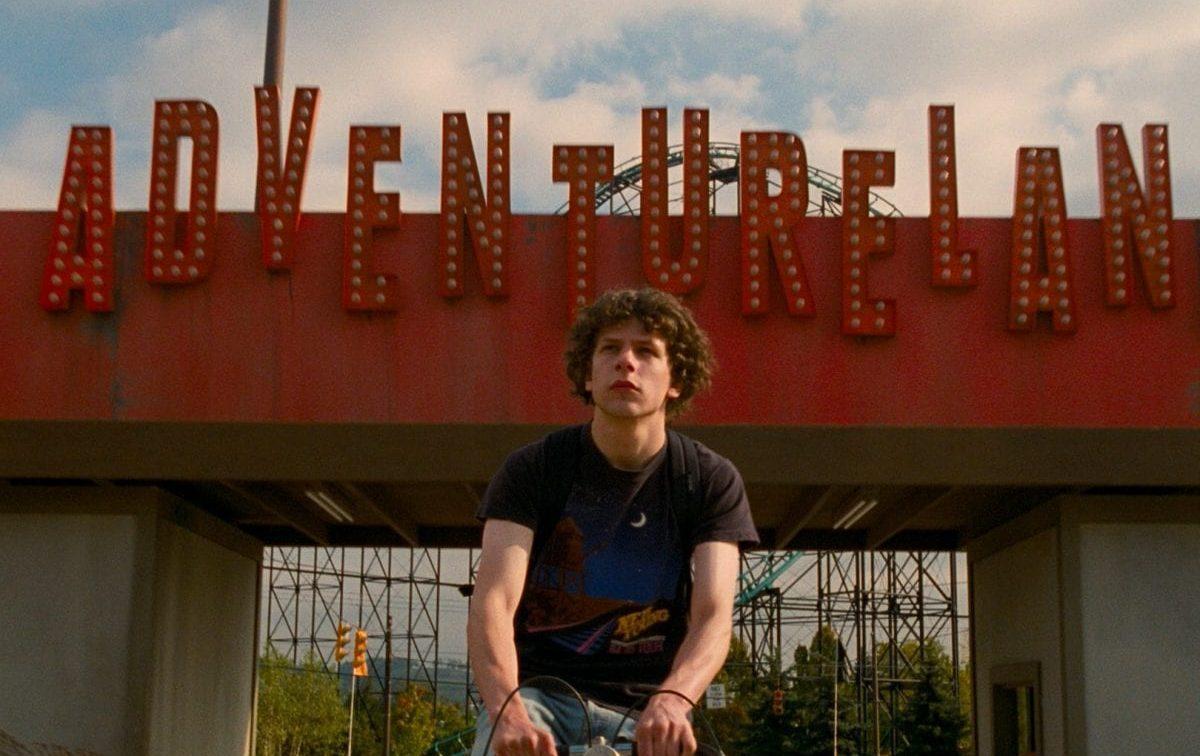 Jesse Eisenberg on a bike as he arrives at the gates of Adventureland