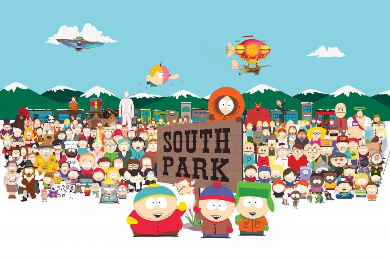 the four main south park characters out in the snow, next to the south park sign with many other charecters behind them