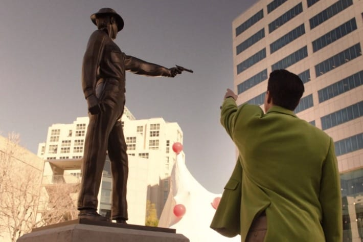 Cooper Dougie from below points his arm at a statue of a lawman holding a gun.