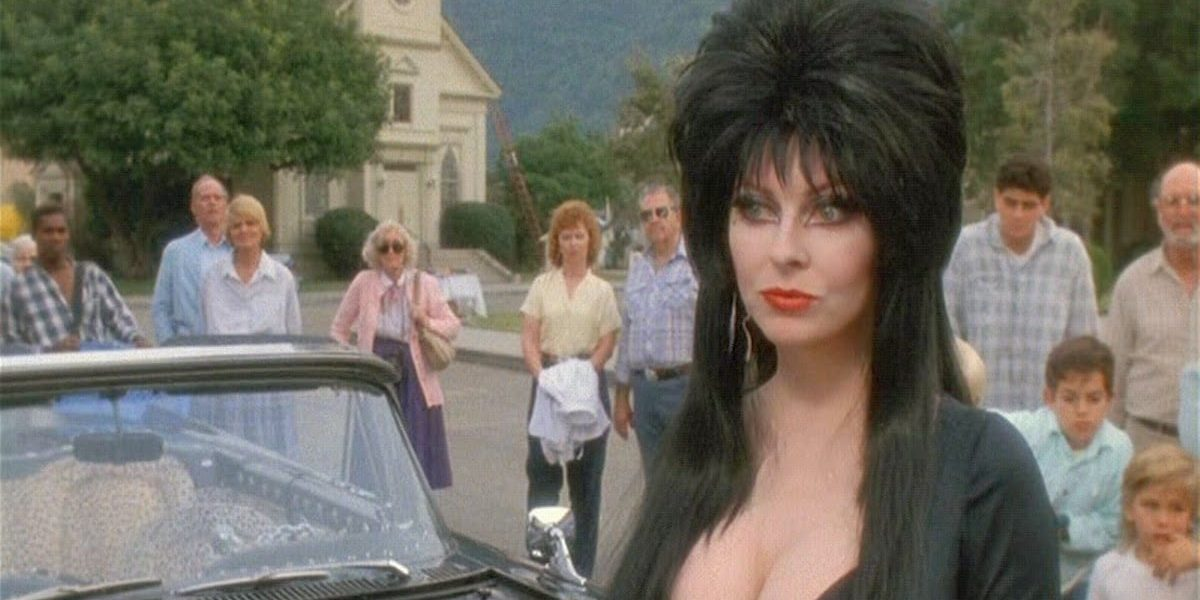Elvira standing next to her convertible on a sunny day, surrounded by curious townspeople.