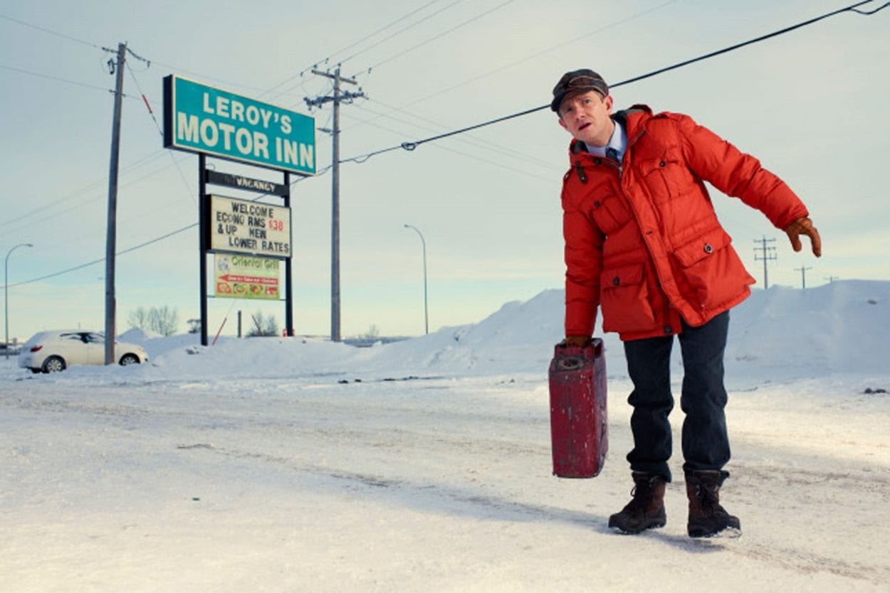 Lester Nygaard stands on a snow covered road with a brief case and wearing an orange coat