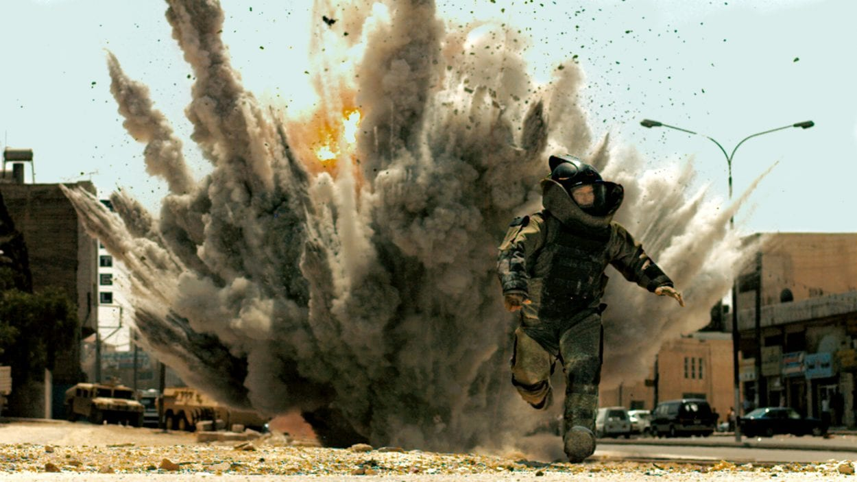 a bomb technician in the bomb suit running from an explosion