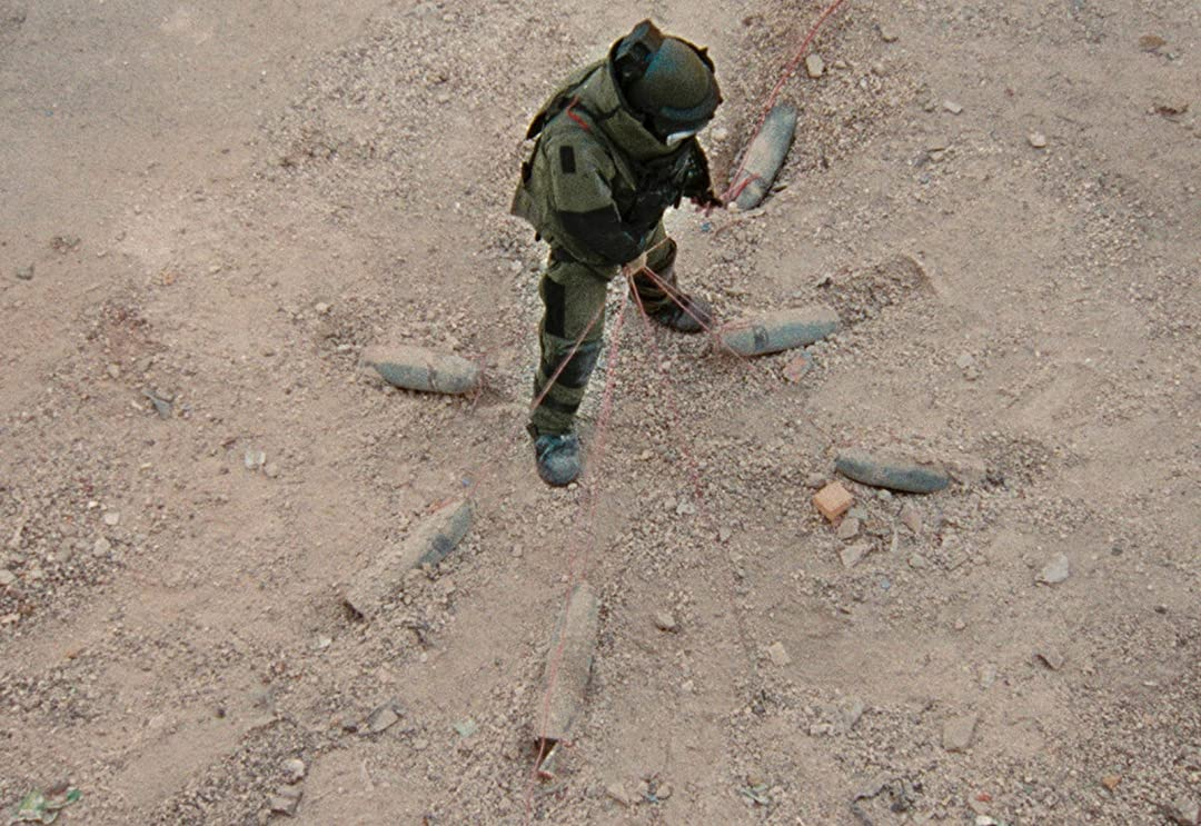 sergeant james in his bomb suit, lifting up a wire that is connected to 6 bombs that surround him