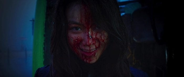 Sook-hee smiles with violent delight with her face covered in blood.