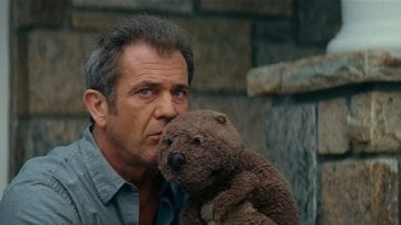 Walter sits on his front porch with a beaver puppet near his face.