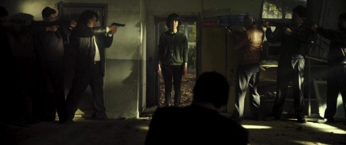 Sook-hee stands in a doorway while a half-dozen assailants aim their guns at her.
