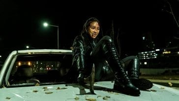 Sook-hee holds onto a car hood in chase.