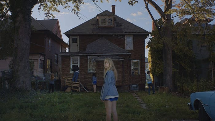 Jay stands at the back of a run down home as her friend investigate the property.