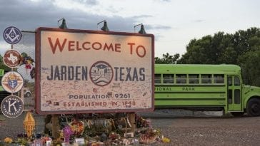 A welcome to Jarden, Texas sign with a school bus passing behind it