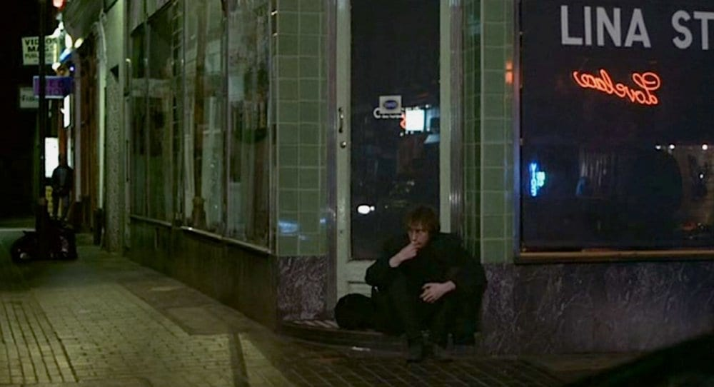 Johnny sits by himself at night outside a closed shop