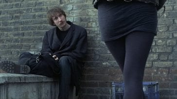 Johnny (in Mke Leigh's Naked, 1993) sits against a brick wall as unknown woman looks over at him