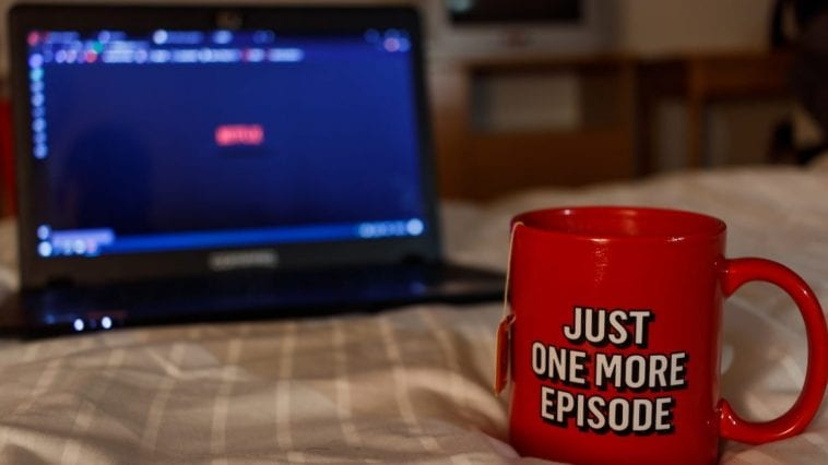"""A mug in front of a laptop with the text """"Just one more episode"""" on it."""