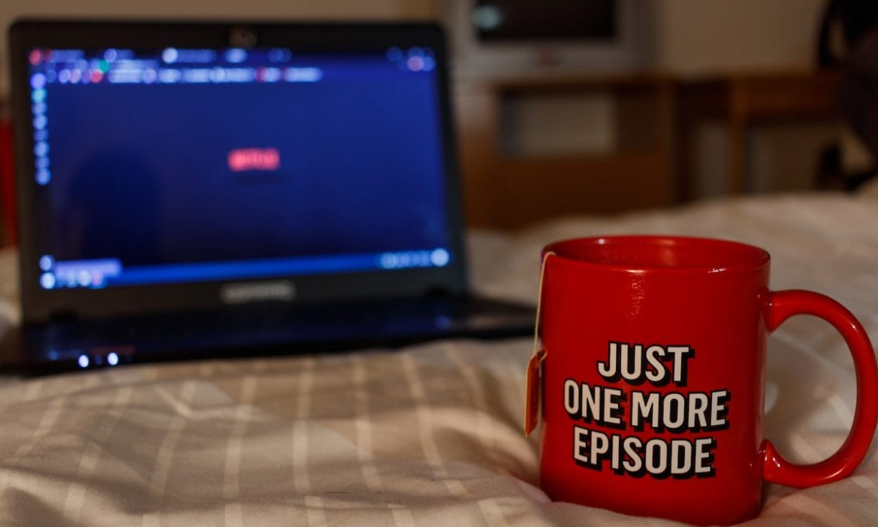 "A mug in front of a laptop with the text ""Just one more episode"" on it."