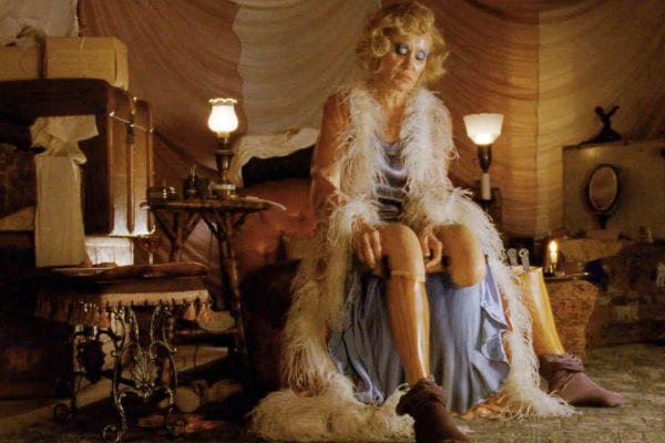 Elsa sits on the edge of her bed, removing her prosthetic wooden legs