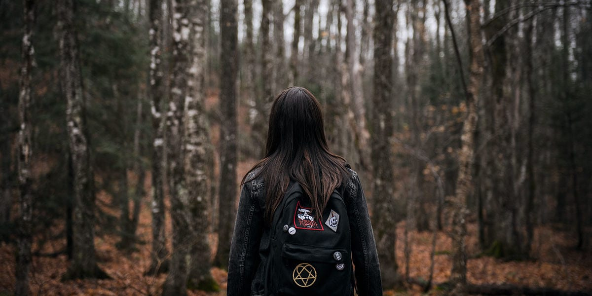 Leah stands in the middle of the woods engulfed by the trees
