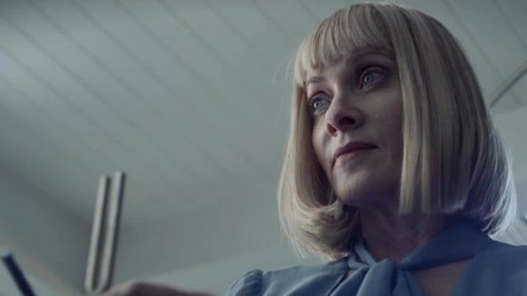 Barbara Crampton as Irma in Sun Choke holding a tuning fork with a wry smile