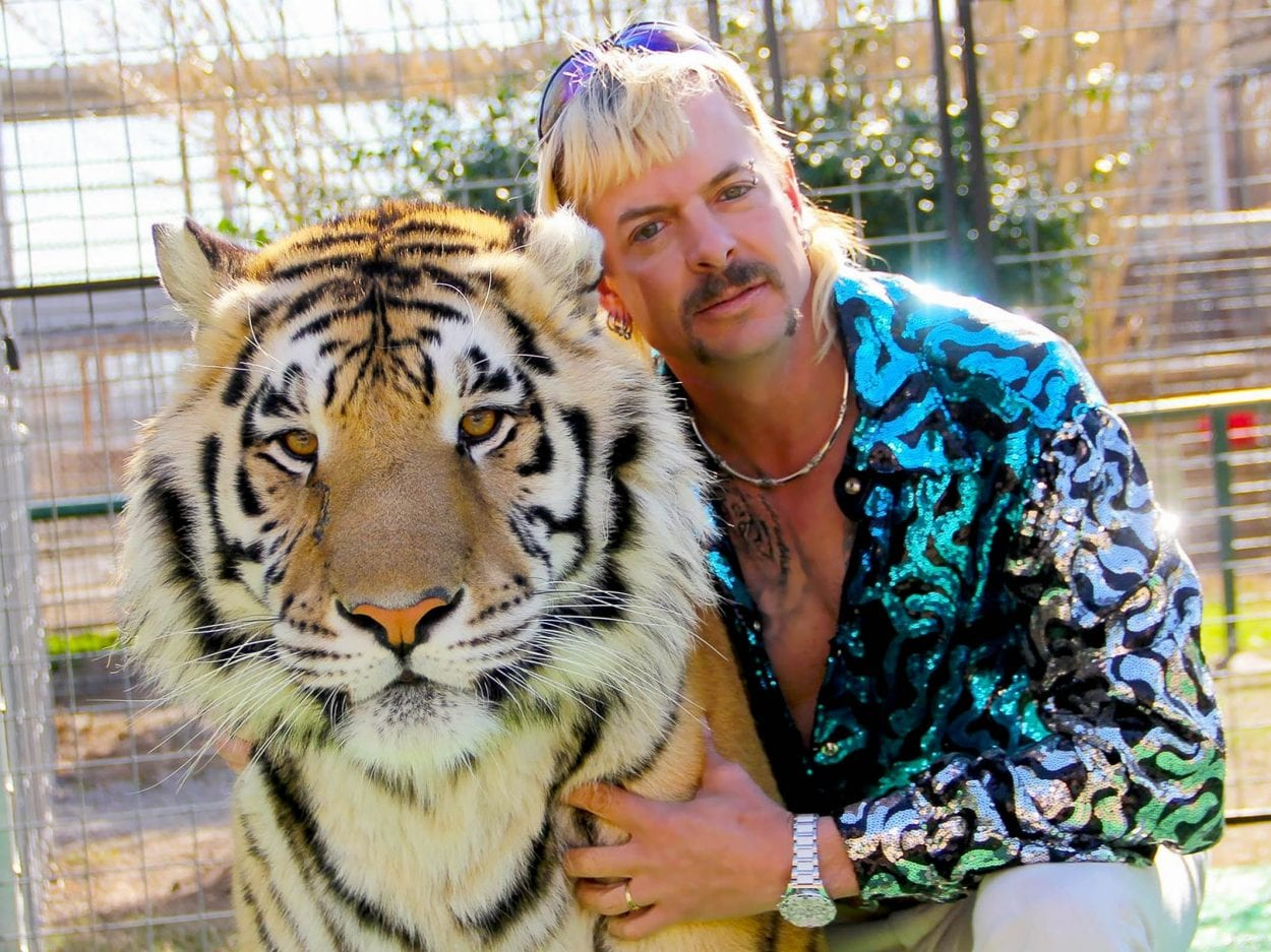 Joe Exotic hunches with his arm around a tiger