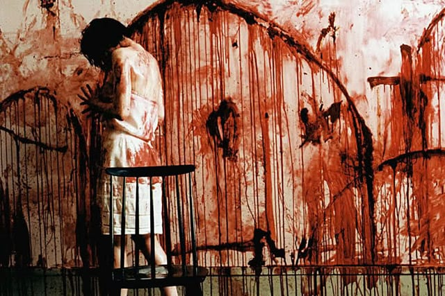 Core walks by a wall covered in blood that she has smeared of the man she just killed