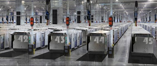 A large warehouse with numbered pods spread throughout.