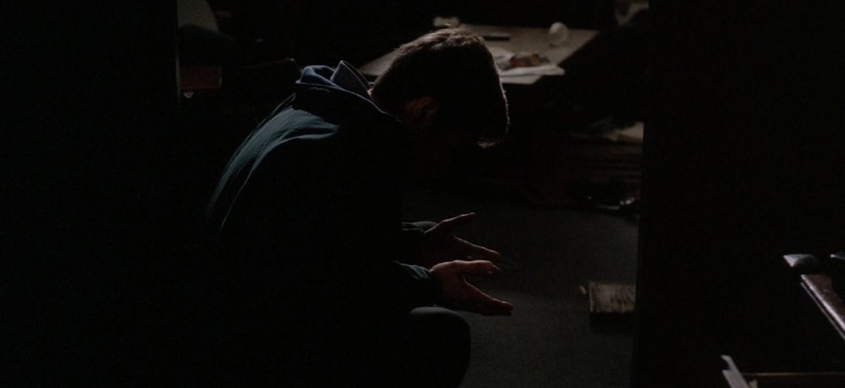 Mulder sits dejectedly on the floor of his ransacked apartment.