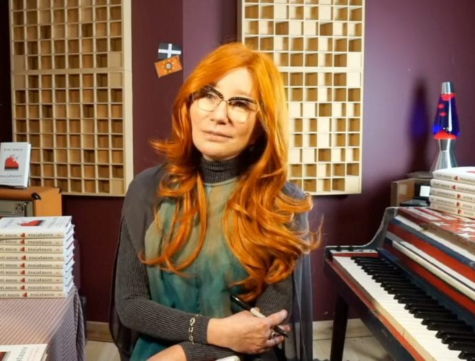 "Tori Amos sits, listening to her daughter (off screen) during a Facebook Live Q&A regarding her book ""Resistance."""