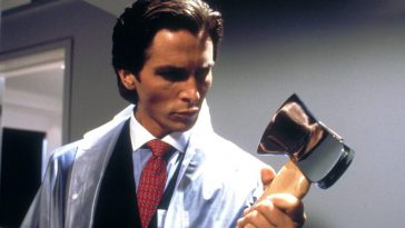Bateman eyes a chrome axe whilst in a see-through raincoat.