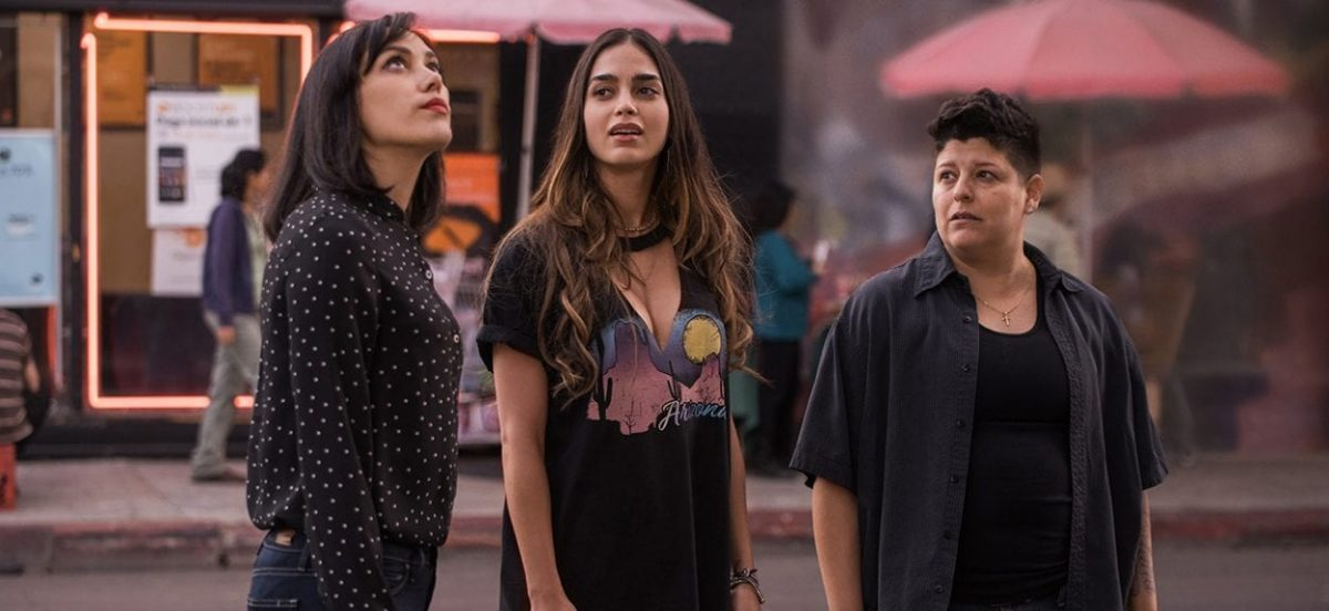 Emma, Lyn, and Eddy (Mishel Prada, Melissa Barrera, and Ser Anzoategui) stand on the street outside their bar looking upwards.