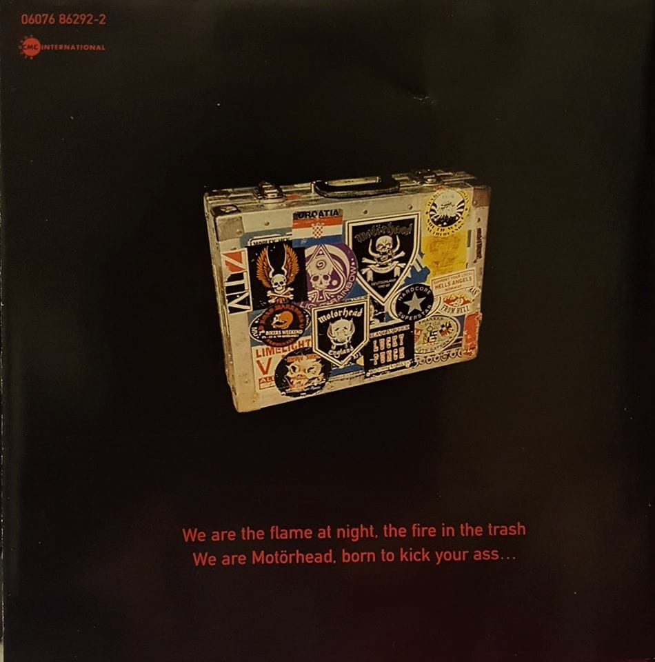 "A metal suitcase adorned with various Motorhead and other rock n' roll stickers, stands upright amidst a black background, with a quote from the song ""We Are Motorhead"" underneath in red letters."