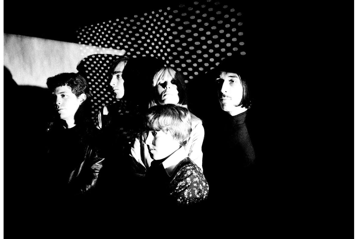 A black and white shot of the band with Nico against a polkadot background