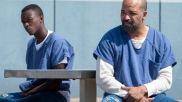 Jahkor sits on an outdoor bench with his father J.D. in prison.