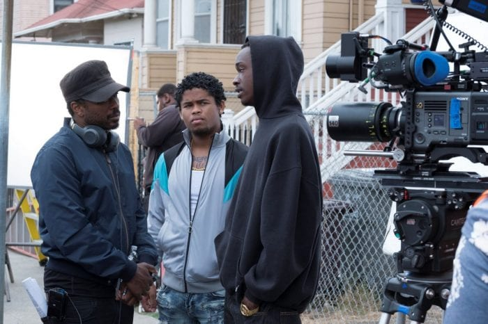 Director Joe Robert Cole speaks with two actors on the set.