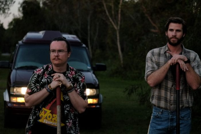 Swin and Kyle look off after burying a body with their shovels