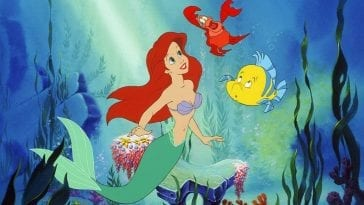 Ariel looking upwards and smiling, Sebastian floating above her, and Flounder looking concerned floating before her with a rock and some seaweed in the background from The Little Mermaid
