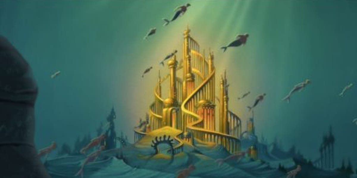 The city of Atlantica, gold and shining brightly amidst the ocean, with merpeople swimming in the foreground in The Little Mermaid