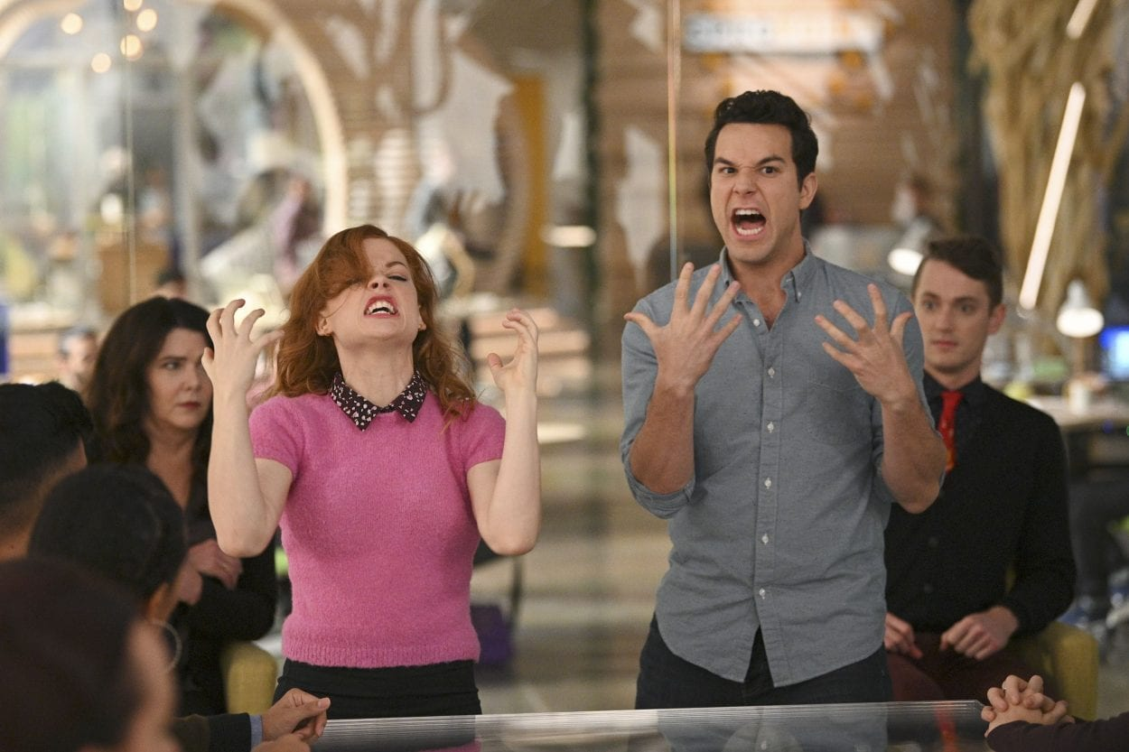 Zoey and Max dance in front of unknowing coworkers.