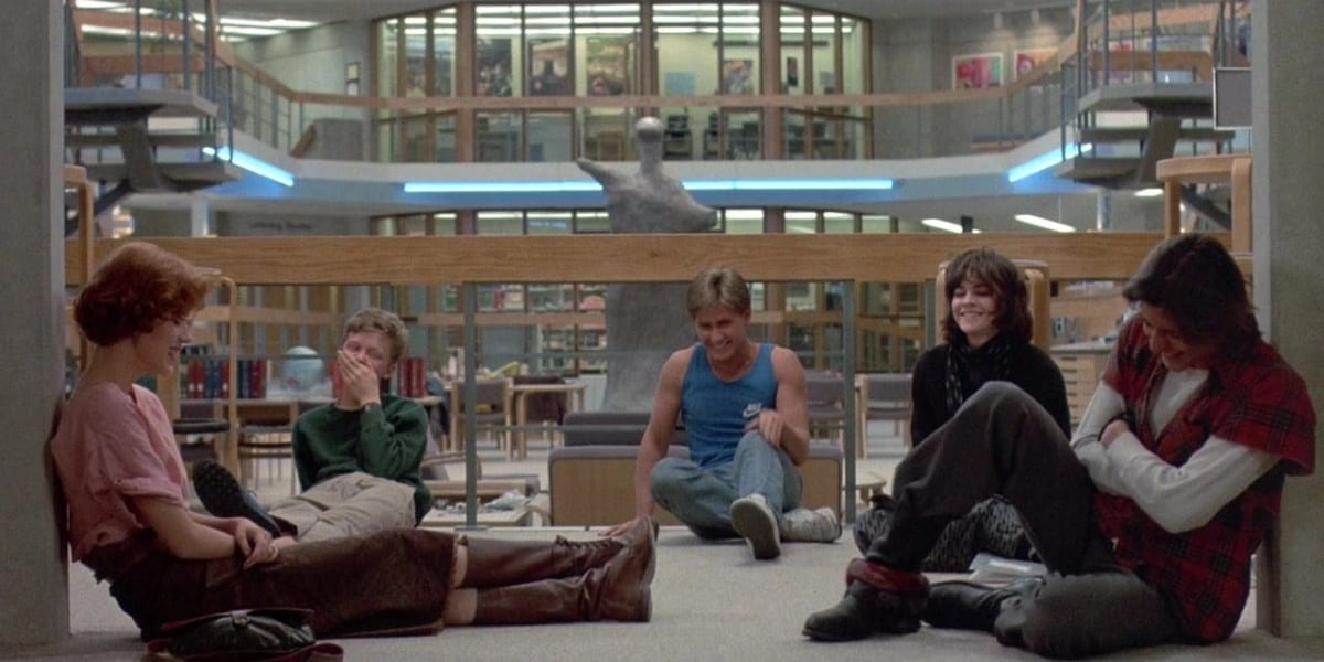 The cast of the Breakfast Club sitting on the floor and laughing in the library