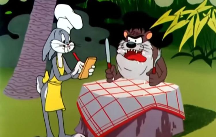 Bugs Bunny, dressed as a chef, takes the order of the impatient Tasmanian Devil, who waits with panting tongue, and fork and knife in hands.