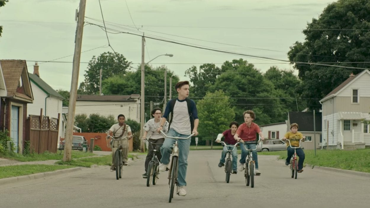 The Losers Club ride bikes down a Derry street.