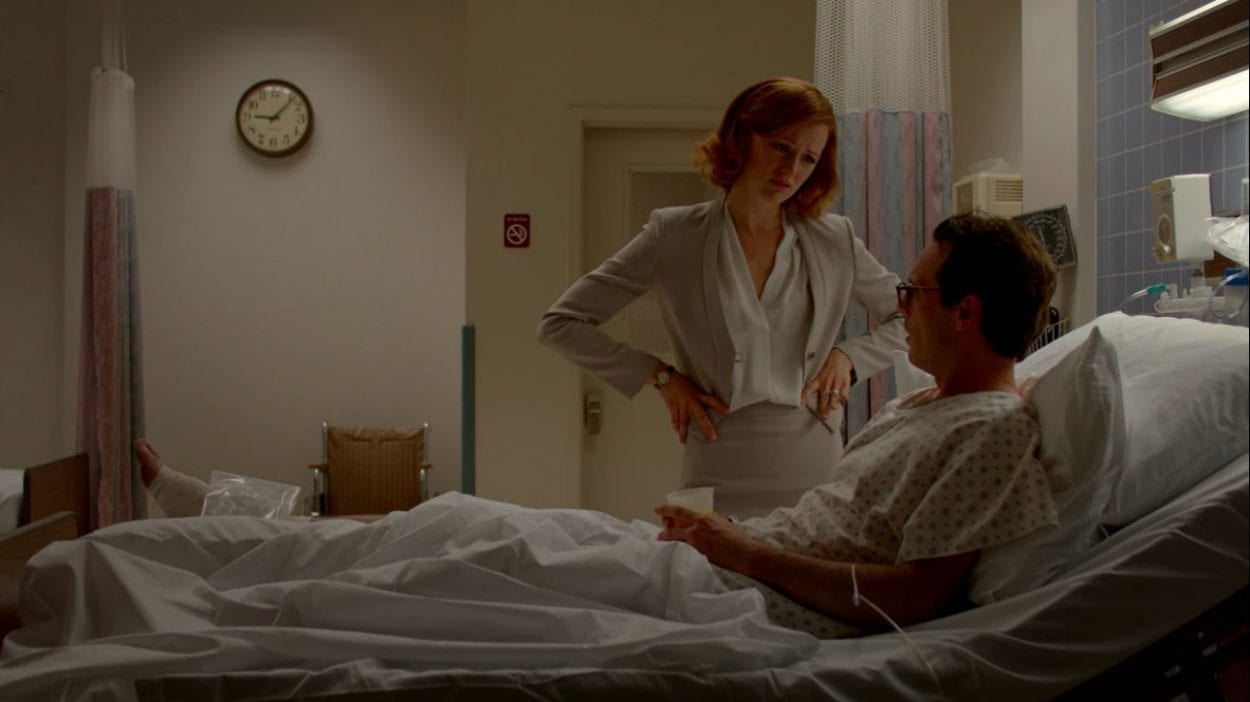 Donna stands next to Gordon's hospital bed with her hands on her hips