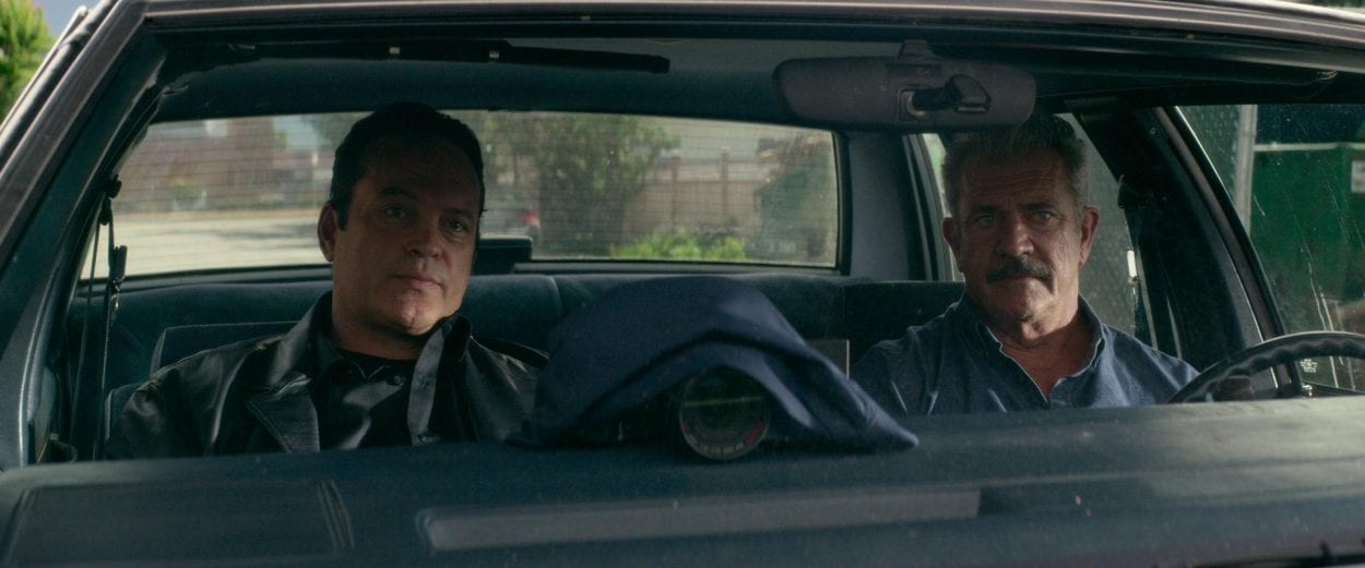 Brett (Mel Gibson) and anthony (Vince Vaughn) gaze towards the scene of a crime during a stakeout in Dragged across Concrete.