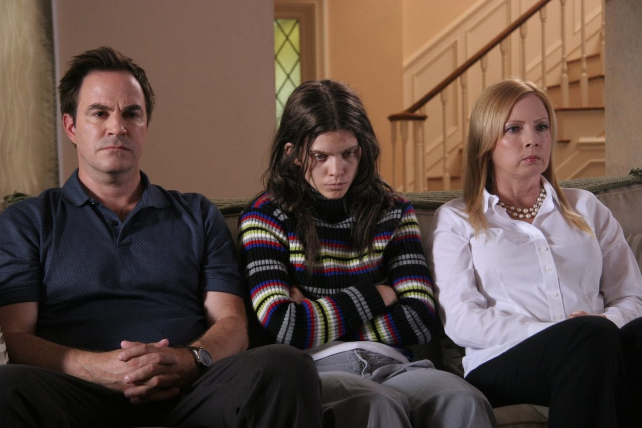 Unhappy family sits on couch.
